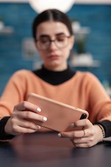 가로 모드에서 스마트폰을 사용하여 온라인 비디오 게임 경쟁을 하는 학생 게이머. 브레이크 시간 동안 모바일 장치로 게임을 하는 거실의 책상 테이블에 앉아 있는 플레이어, 경쟁적인 게이머