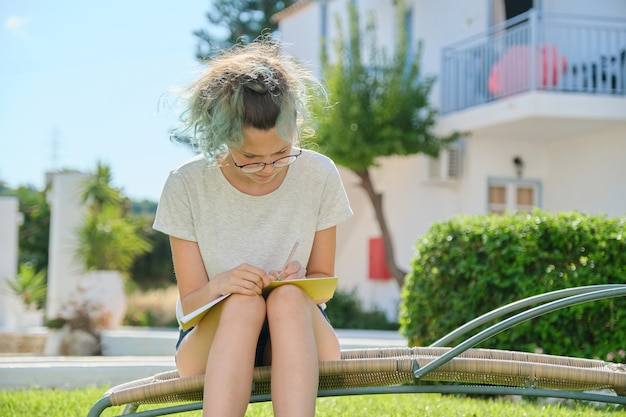 학생 소녀 15, 16 세 야외 앉아, 학교 공책에 쓰기, 집에서 공부하는 여성
