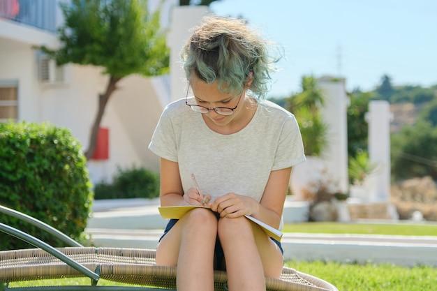 Студент девушка 15, 16 лет сидит на открытом воздухе, пишет в школьной тетради