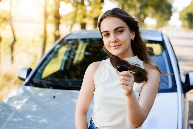 車の購入を自慢し、鍵を見せている学生の女の子