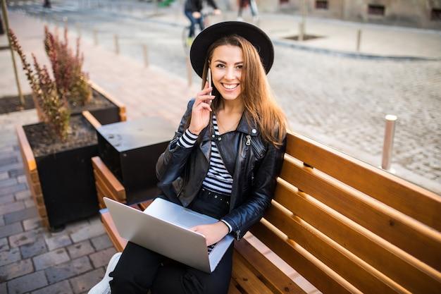 学生少女ビジネスウーマンは秋の日に公園の街の木製ベンチに座る