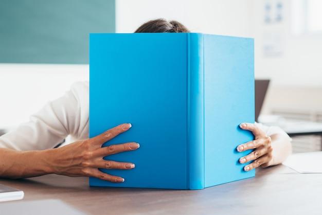 教室で本の後ろに顔を覆っている学生の女の子。