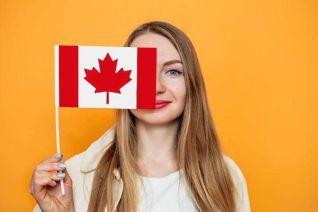 学生の女の子は小さなカナダの旗で半分の顔を覆い、カメラを見ています