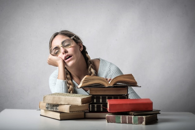 Student girl falling asleep on books