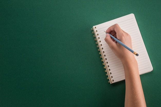 Student of the girl hand from a pencil with notebook on a green background.