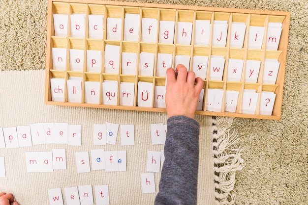 Student girl hand using cards with letters to compose words