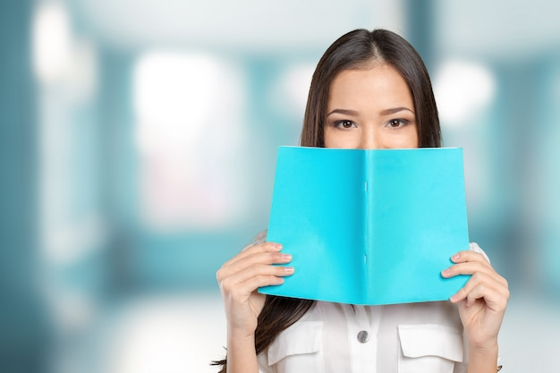 Student girl hides behind the book
