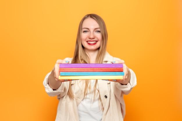 オレンジ色のスタジオの背景に隔離された彼女の手でたくさんの本を持っている学生の女の子