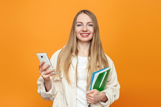 Student girl holding mobile phone and notepad looking at the camera and smiling