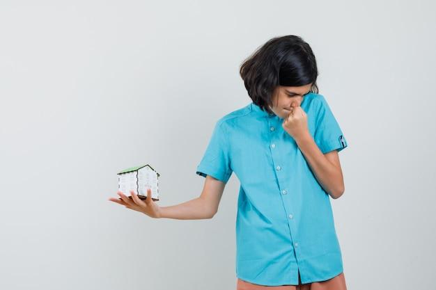 Студентка в синей рубашке держит дом, глядя в сторону
