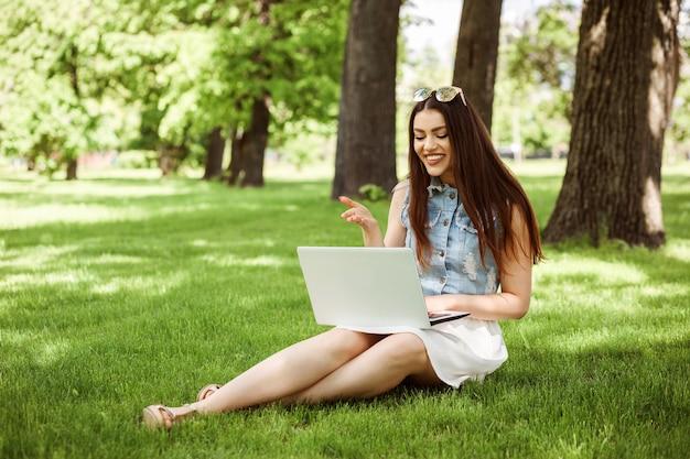 학생 소녀는 여름이나 봄에 공원의 녹색 잔디밭에 앉아 노트북을 사용하여 인터넷으로 통신하고 있습니다.