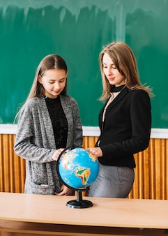 Student girl learning geography with female teacher