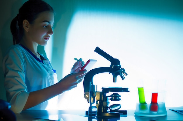 Student girl looking in a microscope, science laboratory concept.