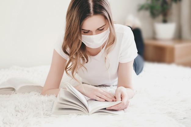 自宅で医療マスクのベッドで横になっていると、本、検疫、コロノウイルス、分離を読んでいる学生の女の子
