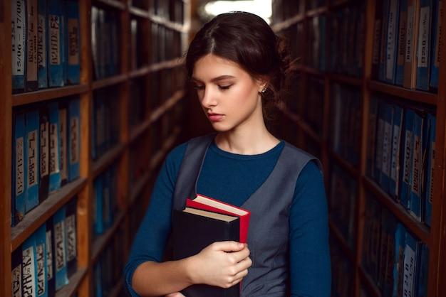 学生の女の子や図書館にある本を持つ女性。