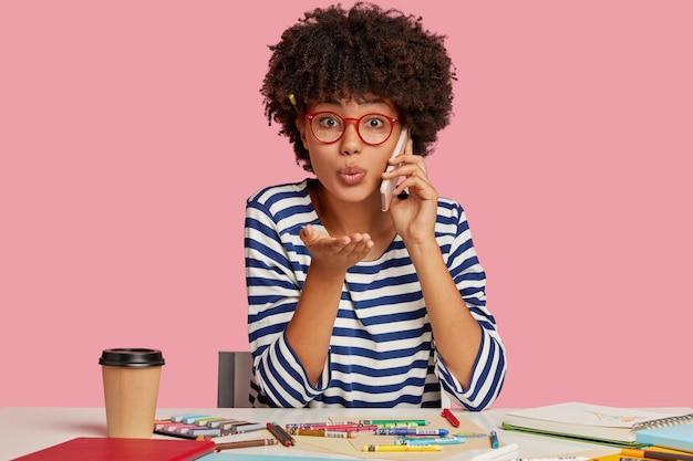 Ragazza studentessa in posa alla scrivania contro il muro rosa