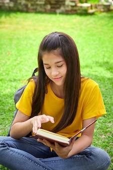 学生の女の子が公園で本を読んで