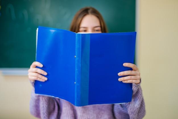 Девушка студента, читая заметки из голубой папки. держите записки перед лицом.