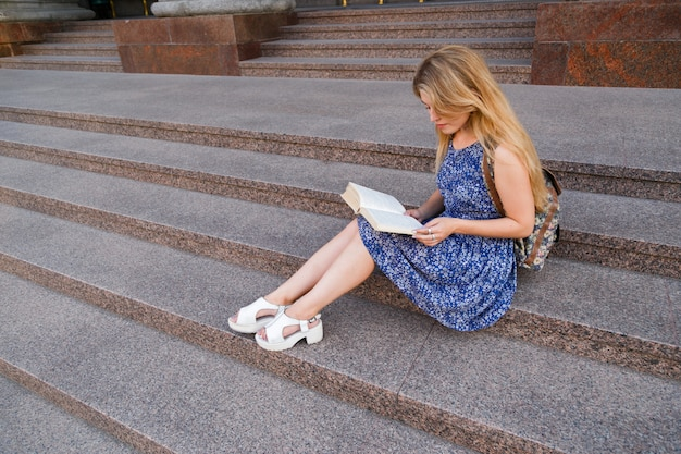 Student girl reading on steps of university.