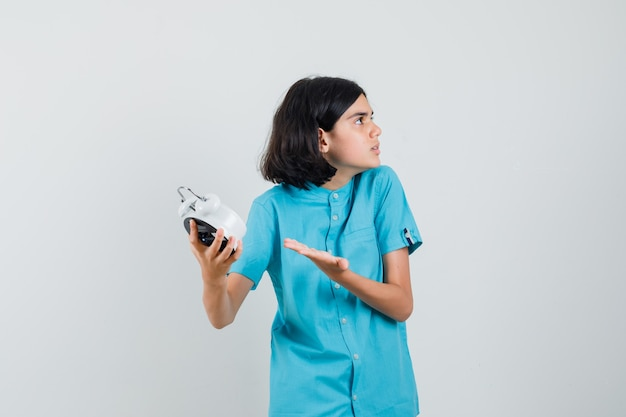 파란색 셔츠에 무언가를 요구하고 공격적으로 보이는 동안 시계를 보여주는 학생 소녀
