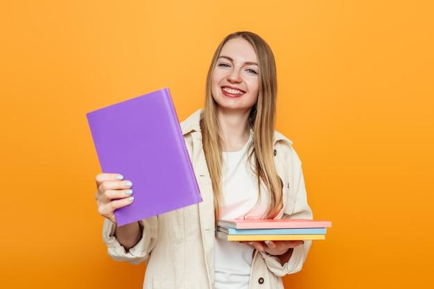 学生の女の子がカメラに1冊の本を見せて、たくさんの本を持っています