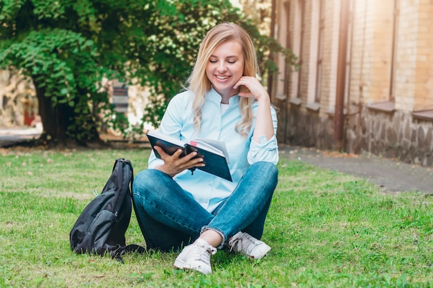 Student girl sits on the grass, reads a book and smiles in a park on a background of university