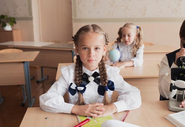Студент девушка сидит за столом, сидя за партой и слушает учителя.