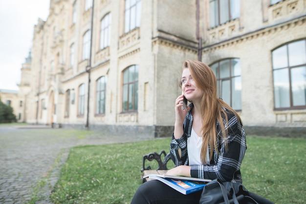大学のキャンパスのベンチに座って、膝の上に本を置き、電話で話して、笑っている学生の女の子。