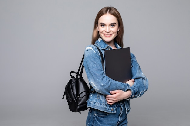 Student girl smiling at camera, pressing laptop to chest, wearing backpack, ready to go to studies, start new project and suggest new ideas isolated on gray wall
