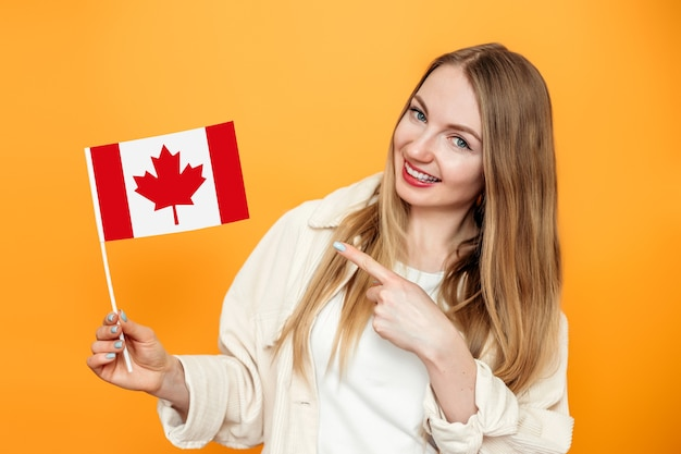 Student girl smiling and pointing a finger at small canada flag