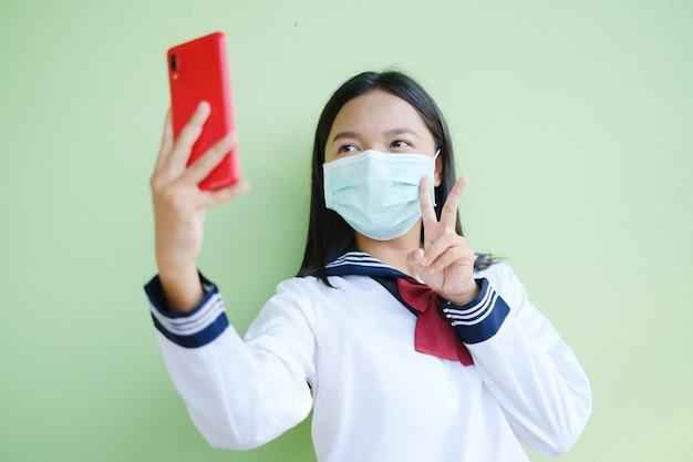 Student girl wear mask make selfie by smartphone