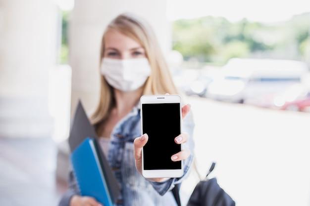 医療マスクを身に着けている学生の女の子は、空の画面で携帯電話を示しています