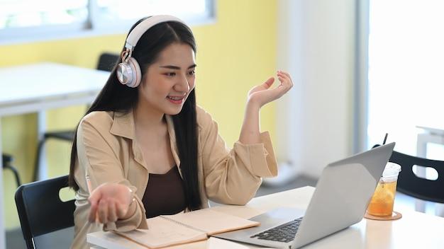 オンラインで学習し、コーヒーショップに座っているラップトップコンピューターを介してビデオ通話をしているヘッドフォンを身に着けている学生の女の子。