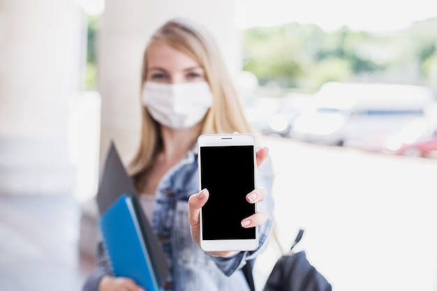 Student girl wearing a medical mask shows a mobile phone with empty screen