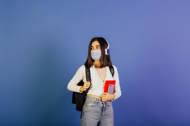 学生の女の子は、ヘッドフォンと青い表面に分離された黒いバックパック付きの医療用マスクを着用しています。