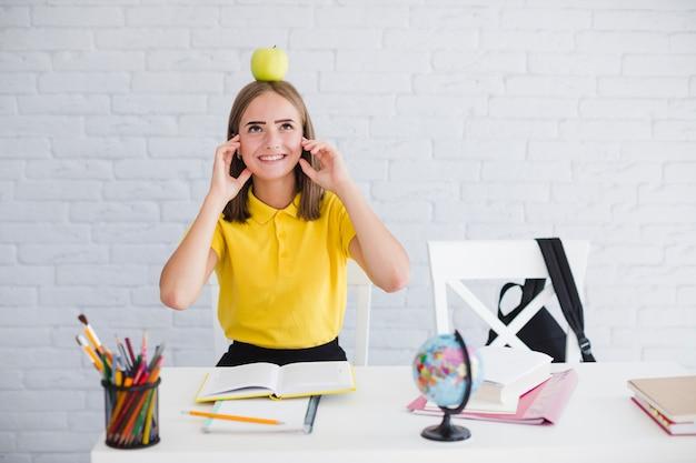 Студенческая девушка с яблоком на голове