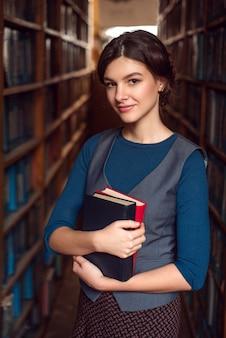 本棚の間の本を持つ学生の女の子