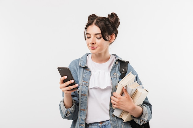 Student girl with double buns hairstyle wearing jeans clothing and backpack using smartphone while holding studying books, isolated on white wall