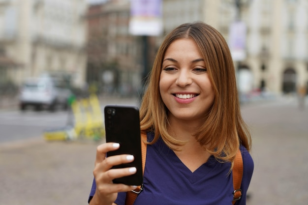 Student girl with smartphone chatting with her friends on blurry city background