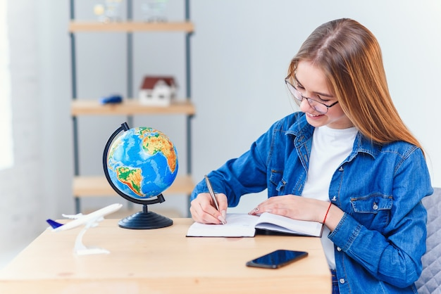 Student girl writes in notebook while studying at white living room. studying geography with globe. cute schoolgirl in denim clothes makes hometask.