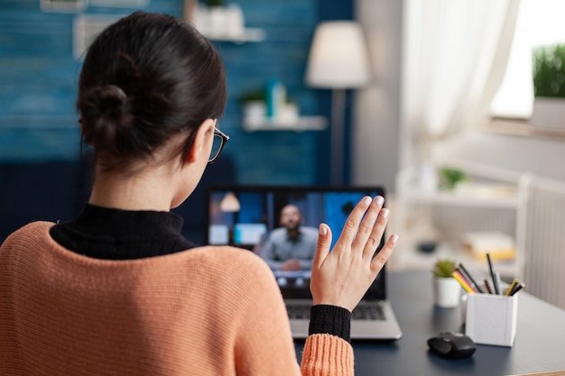 Student greeting her school teacher during online videocall meeting. young woman talking about math lesson on university webinar while sitting at desk table in living room