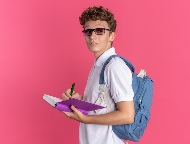 Studente in abiti casual con gli occhiali con lo zaino che tiene il libro