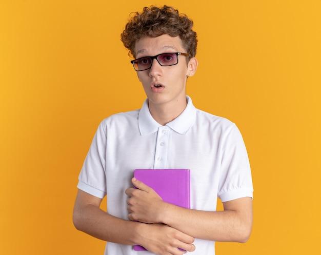 Studente in abbigliamento casual con gli occhiali con in mano un libro che guarda la telecamera stupito e sorpreso