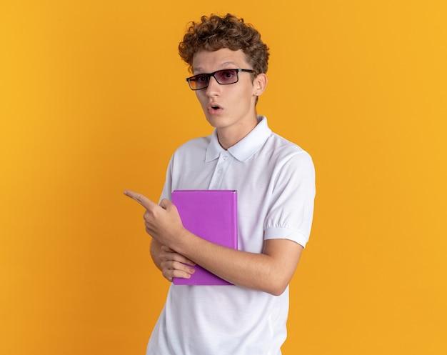 Ragazzo studente in abbigliamento casual con gli occhiali che tiene un libro guardando la telecamera sorpreso che punta con il dito indice a lato in piedi su sfondo arancione