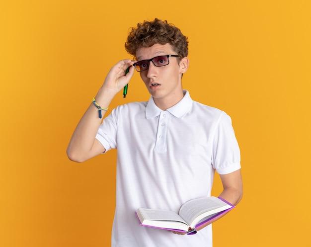 Studente in abbigliamento casual con gli occhiali con in mano un libro e una matita che guarda la telecamera sorpreso