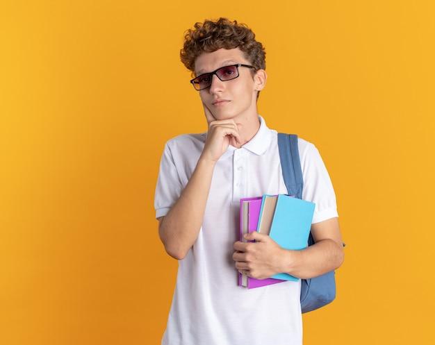 Ragazzo studente in abbigliamento casual con gli occhiali con zaino in mano libri guardando la telecamera