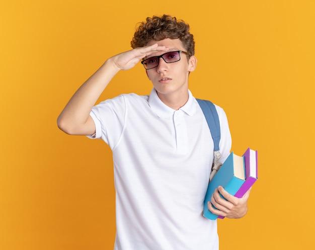 Ragazzo studente in abbigliamento casual con gli occhiali con zaino in mano libri che guarda lontano con la mano sopra la testa in cerca di qualcuno