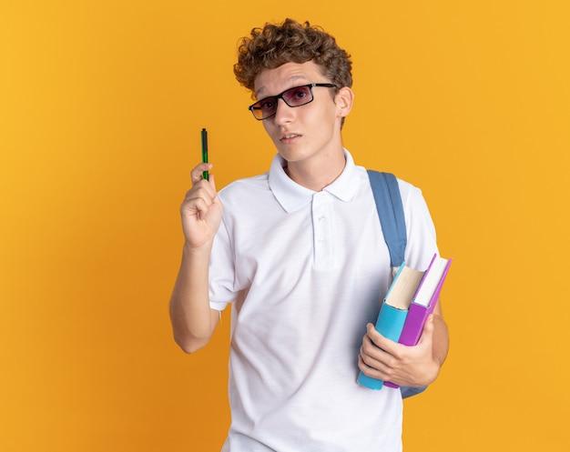 Ragazzo studente in abbigliamento casual con gli occhiali con lo zaino che tiene libri