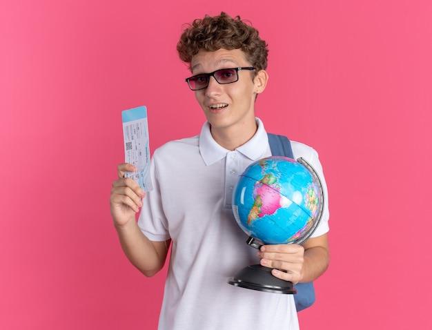 Ragazzo studente in abbigliamento casual con gli occhiali con lo zaino che tiene il globo e il biglietto aereo guardando la telecamera sorridendo allegramente in piedi su sfondo rosa