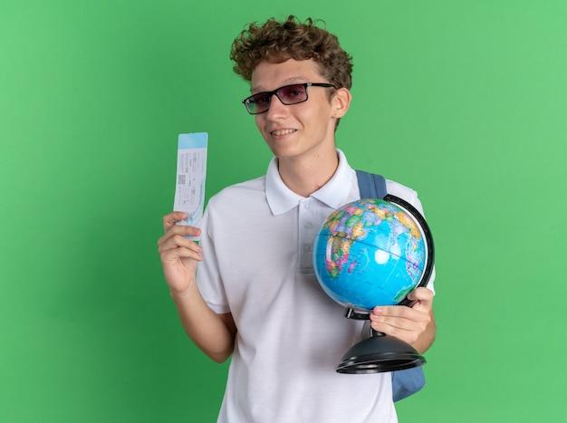 Ragazzo studente in abbigliamento casual con gli occhiali con lo zaino che tiene il globo e il biglietto aereo sorridendo fiducioso guardando la telecamera